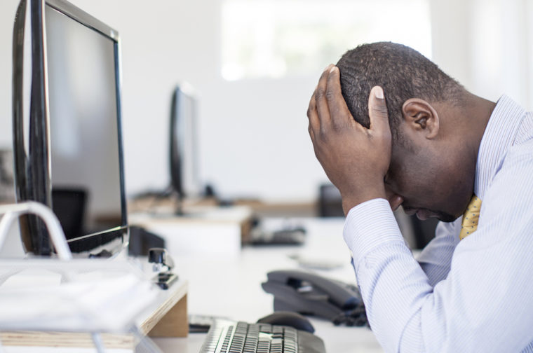 Stressed african businessman sitting at his desk.